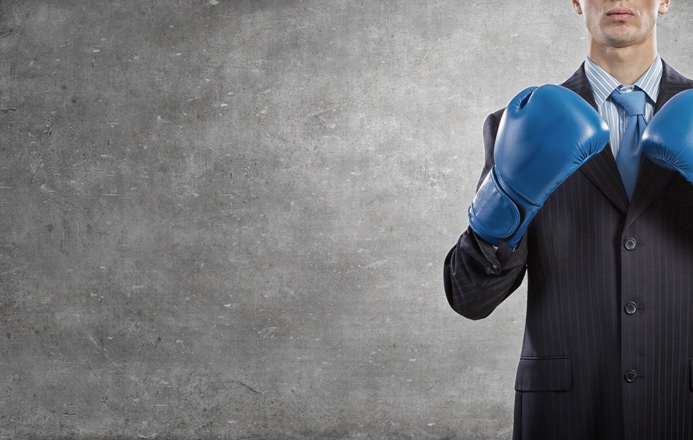 Determined businessman in suit and boxing gloves